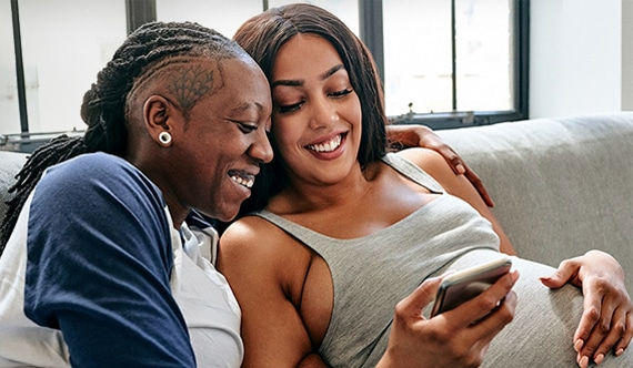couple messaging their doula on their phone